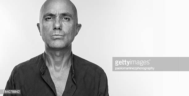 bald man in black shirt looks with concern - black and white stock-fotos und bilder