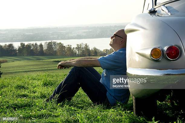 bald man sitting on meadow by his classic car
