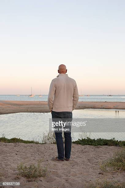 Bald man standing on a sandy beach by the ocean.
