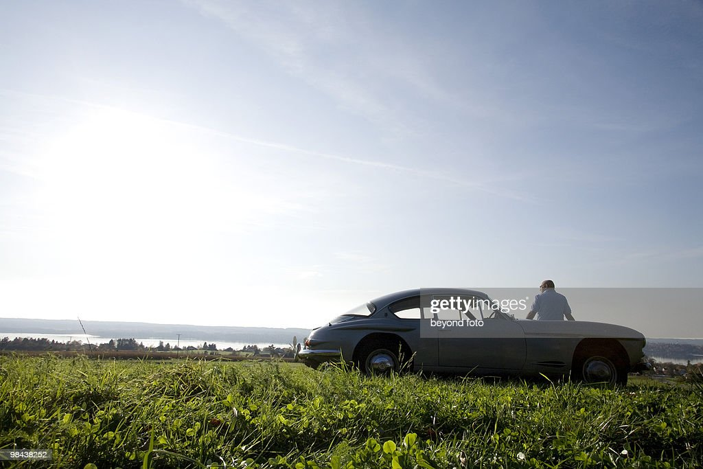 bald man standing on meadow by his classic car watching landscape : Stock Photo