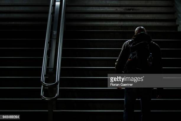 A bald man walks up a flight of stairs in the dark on April 06 2018 in Berlin Germany