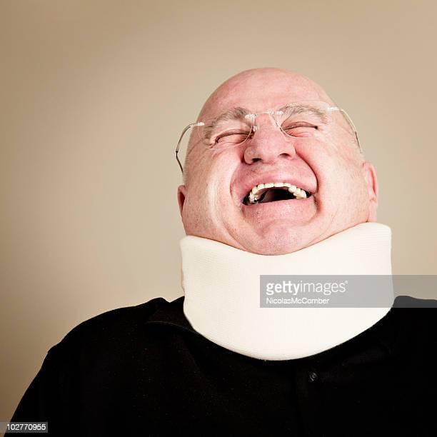 Bald man wearing a neck brace laughing