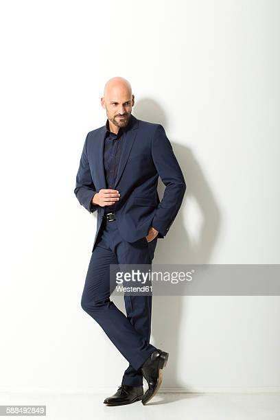 bald man with beard wearing blue suit standing in front of white background - omlaag kijken stockfoto's en -beelden