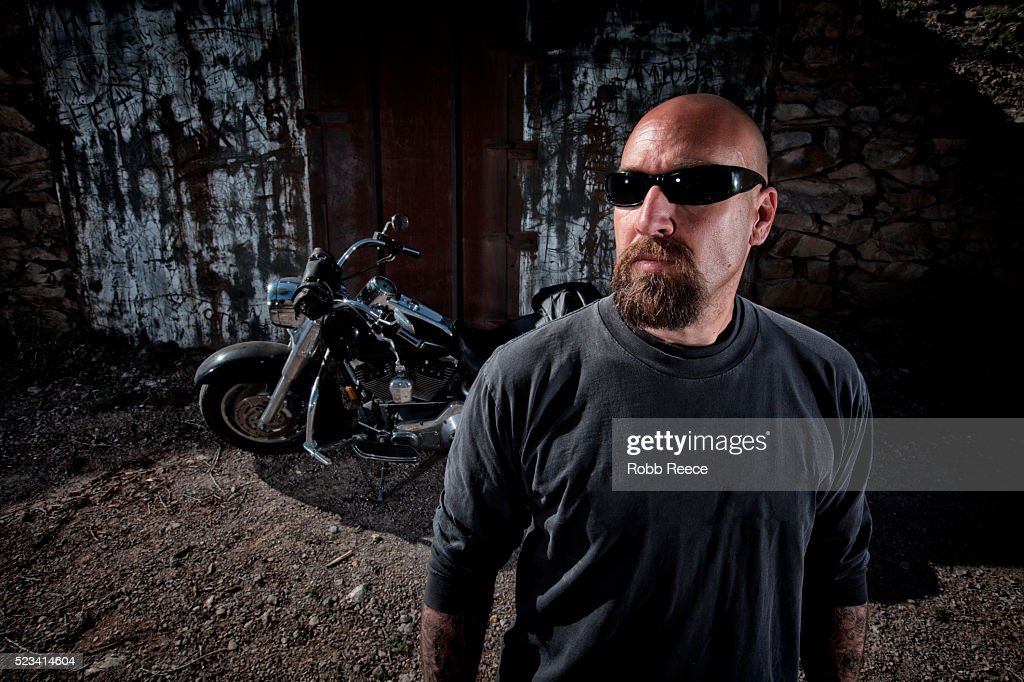 Bald man with his motorcycle behind : Stock Photo
