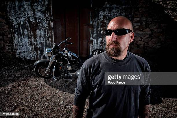 bald man with his motorcycle behind - robb reece stockfoto's en -beelden