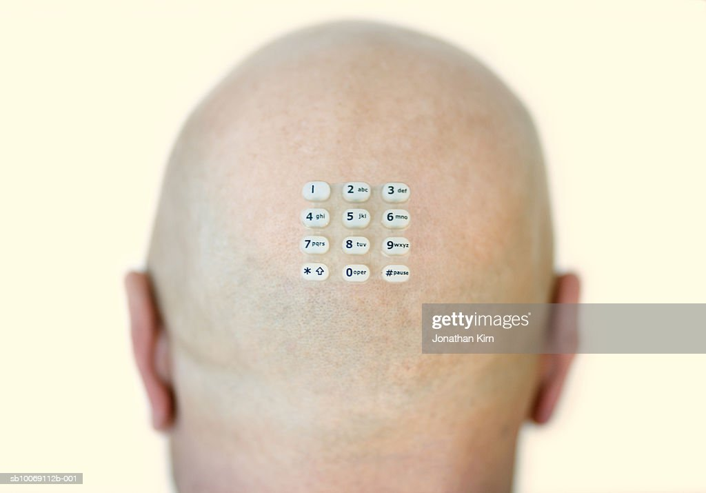 Bald man with keypad stuck on head : Stockfoto