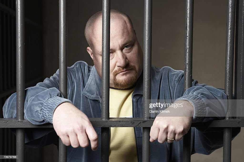 Bald mid-adult man standing behind prison bars : Stock Photo