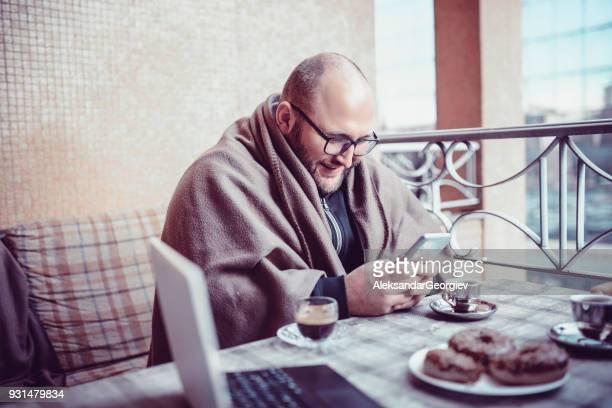 Kahle Männer mittleren Alters trinken Kaffee und Lesen der Nachrichten auf dem Handy
