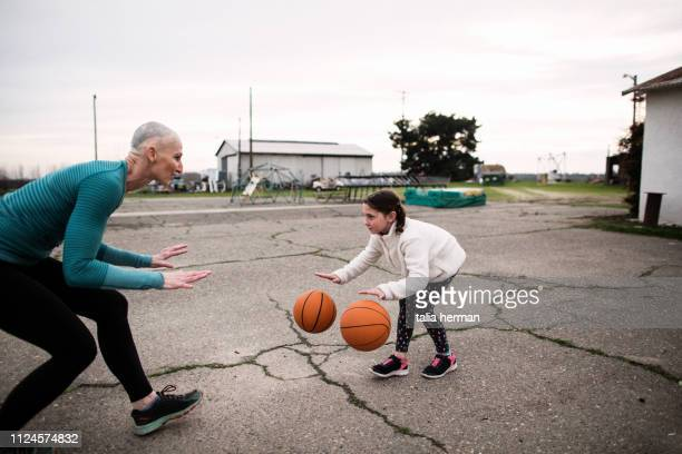 bald mother and basketball coach trains twin daughters - showus stock pictures, royalty-free photos & images