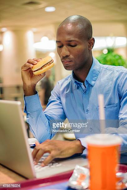 Bald office worker eating burger while typing on laptop