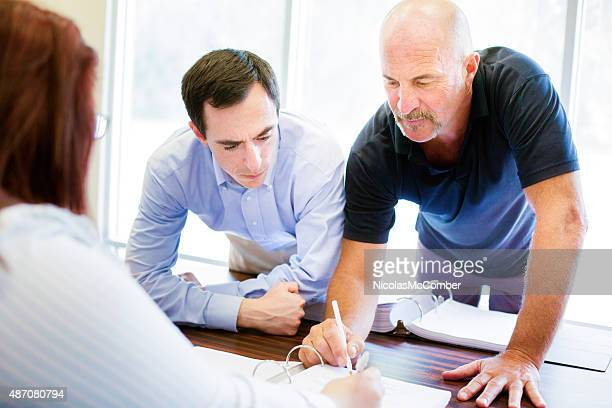 Bald office worker explains policy to colleagues