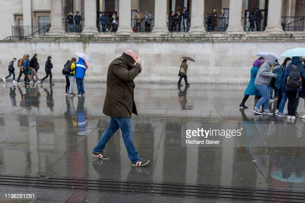 A bald pedestrian walks through rain beneath the columned architecture of the National Gallery in Trafalgar Square Westminster on 9th April 2019 in...