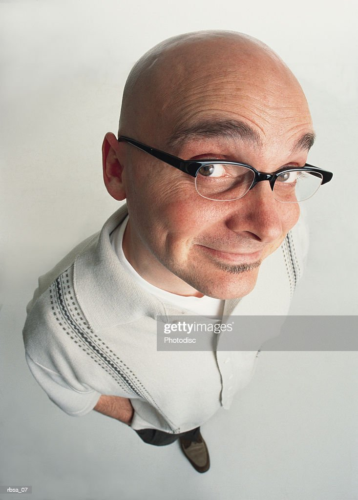 bald young adult caucasian male with facial hair and glasses stands looking up at the camera with an expressive grin : Foto de stock