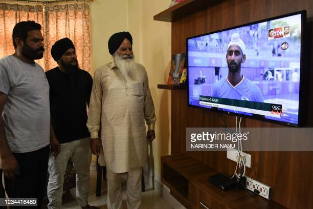 Baldev Singh , father of India's field hockey player Gurjant Singh along with relatives watch the television as India's team lost the men's...