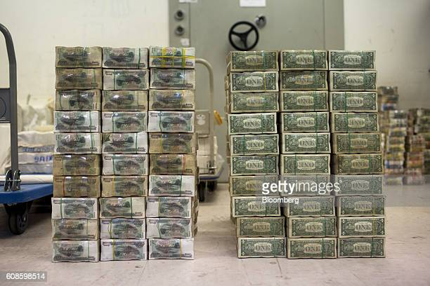 A bale of Cambodian 5000 riel banknotes left stands next to a bale of US one dollar notes at an Acleda Bank Plc branch in Phnom Penh Cambodia on...