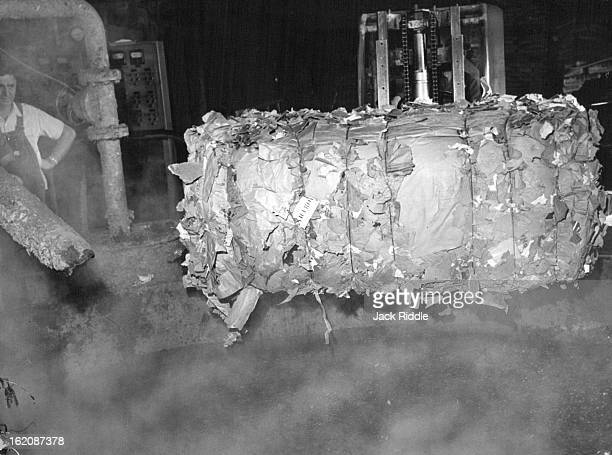 DEC 1965 DEC 13 1965 A bale of shredded scrap paper and cardboard is dumped into a steaming pulp tank as the first step in making paperboard at the...