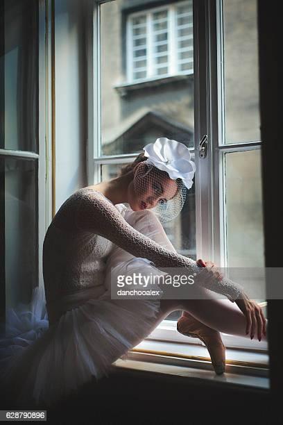 Balerina sitting in window frame