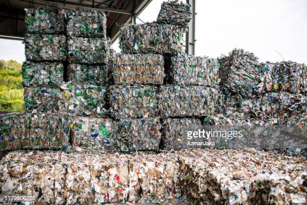 bales of compressed recyclable materials stacked outdoors - recycling stock pictures, royalty-free photos & images