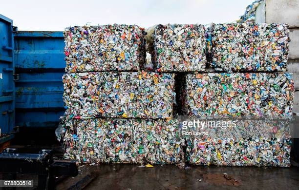 bales of crushed aluminum cans at a recycling plant
