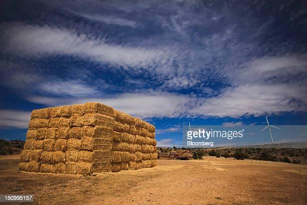 Bales of straw sit in a field near turbines at an Iberdrola SA wind farm in Maranchon near Calatayud Spain on Wednesday Aug 29 2012 Spanish Budget...