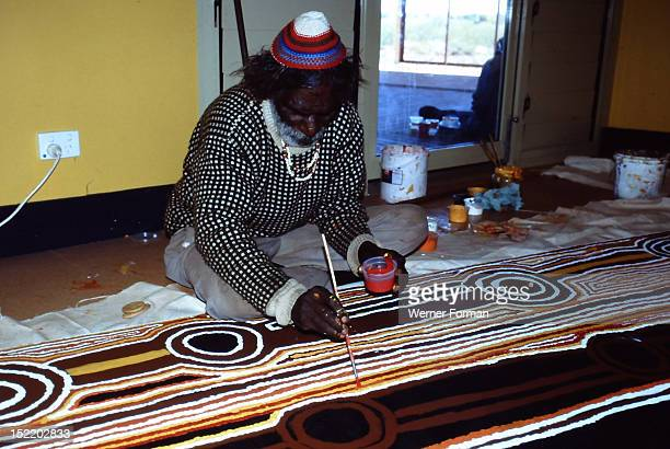 Balgo Community desert artist the late Tjumpo Tjapanangka working on a dot painting at the Warlayirti Culture Centre in the northwest desert region...