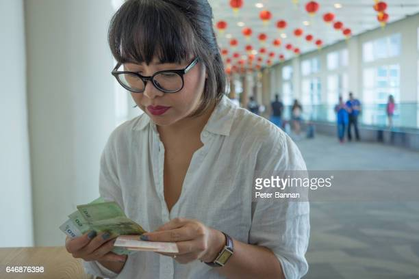 Bali, Indonesia, Asian woman at airport departures, counting money