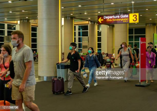 bali international airport passengers travel people wearing masks to protect from covid-19 coronavirus - tourism stock pictures, royalty-free photos & images