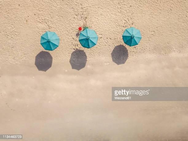 bali, kuta beach, three beach umbrellas, aerial view - parasol de plage photos et images de collection