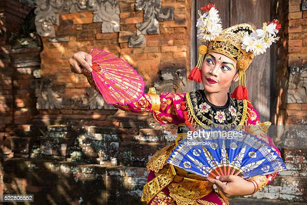 Bali performing dancer in a temple with fans
