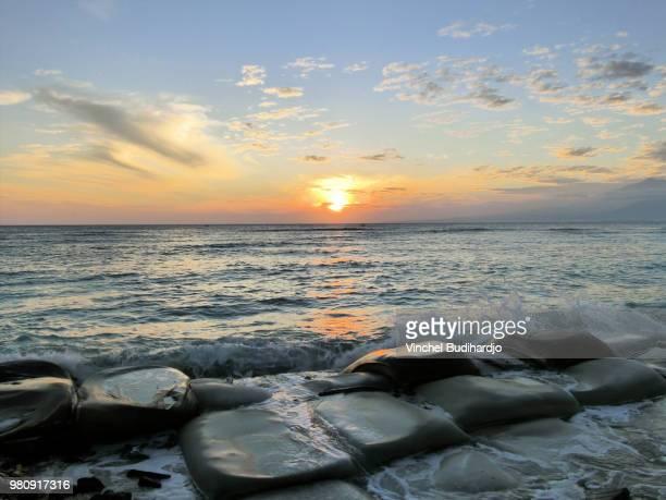 bali sea and rocks at sunrise, gili trawangan, indonesia - gili trawangan bildbanksfoton och bilder