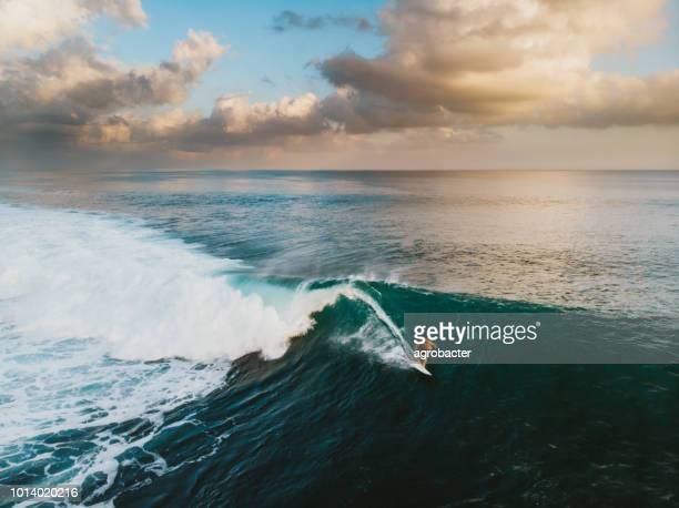 bali surf zone surfer riding a wave - wave stock pictures, royalty-free photos & images