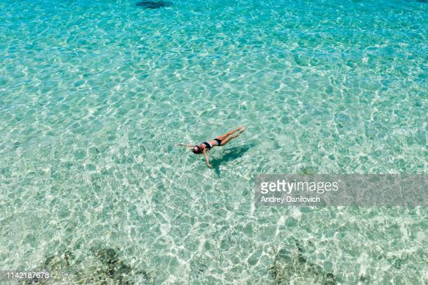 bali, woman floating in transparent turquoise sea. aerial drone shot. - bay of water stock pictures, royalty-free photos & images