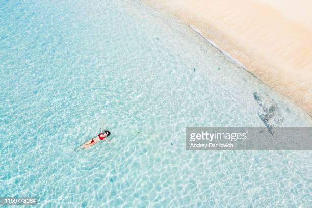 bali, femme flottant dans la mer turquoise transparente. tir de drone aérien. - femme maillot de bain photos et images de collection