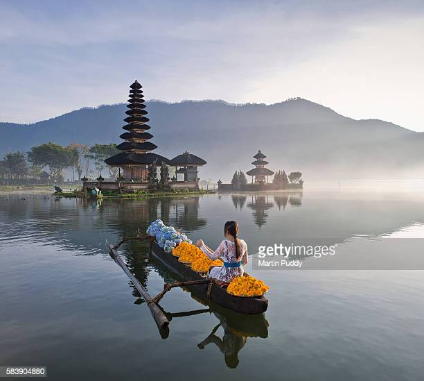 Bali, woman rowing boat infront of Ulun Danu Bratan temple