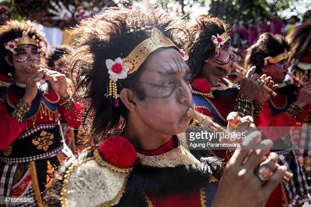 Balinese artist plays bamboo flute during a parade of the opening 37th Bali International Arts Festival on June 13 2015 in Denpasar Bali Indonesia...