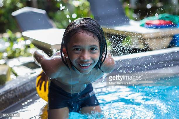 Balinese boy playing in swimming pool
