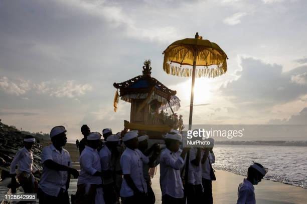 Balinese carries effigies and deities during Melasti a purification ceremony ahead of the holy day of Nyepi on Purnama Beach in Gianyar Bali...