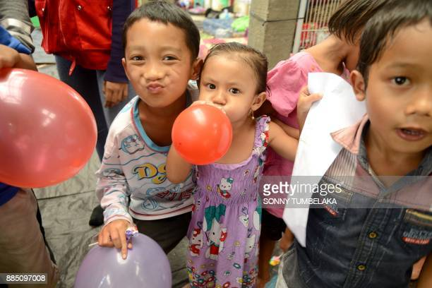 Balinese children show their drawings and play with balloons at an evacuation center after being evacuated from Mount Agung volcano at Rendang in...