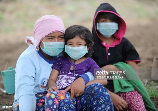 Balinese children wear masks as Mount Agung erupts in Kubu subdistrict in Karangasem Regency on Indonesia's resort island of Bali on November 27 2017...