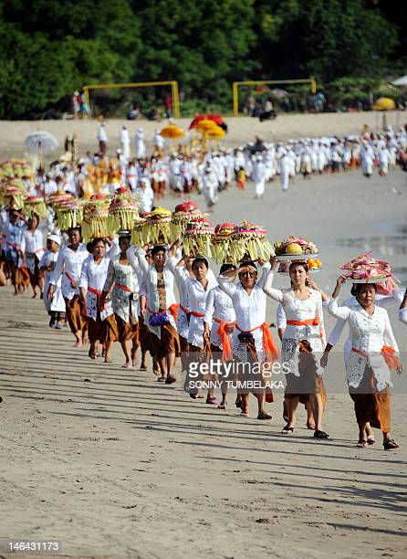 Balinese dressed in traditional clothing carry offerings on their heads during a Melasti ceremony prayer at Kuta in Denpasar on the island of Bali on...