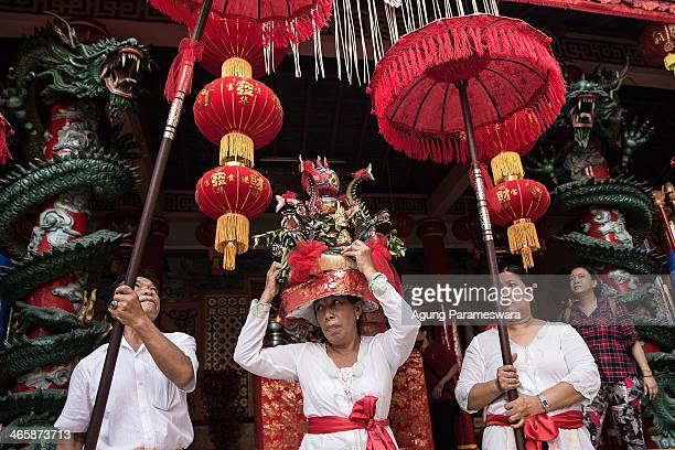 Balinese ethnic Chinese woman carries holy water during the Ngelawang Ritual at Dharmayana Chinese Temple on January 30 2014 in Kuta Indonesia...