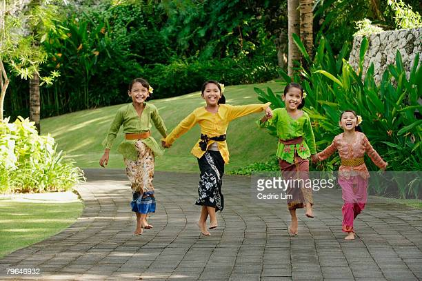 Balinese girls laughing and running