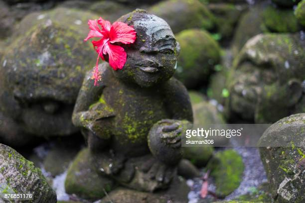 Balinese God sculpture cover by fern rain forest