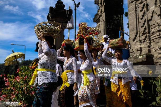 Balinese Hindu carry offering as they pray during the Melasti ritual ceremony at Ulun Danu Beratan Temple in Bali Indonesia on March 4 2019 The...