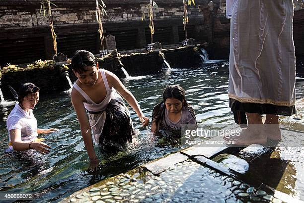 Balinese Hindu devotees perform the Banyu Pinaruh ritual at Tirta Empul holy spring on October 5 2014 in Gianyar Bali Indonesia Banyu Pinaruh is a...