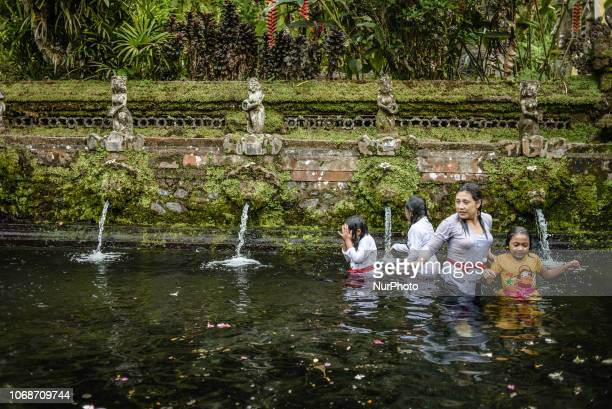 Balinese Hindu family during the Melukat ceremony at Pura Gunung Kawi Sebatu Temple Bali Indonesia on November 22 2018 The Melukat ceremony aims to...