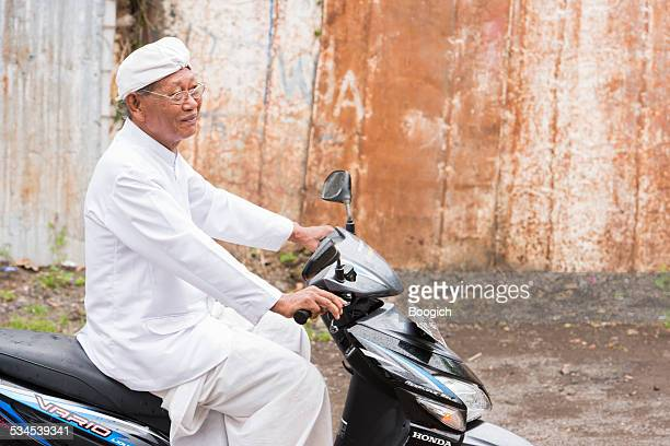 balinese hindu priest rides to traditional ceremony - balinese culture stock pictures, royalty-free photos & images
