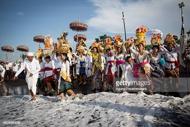 Balinese Hindus devotees carry Pratima statues and offerings during Melasti Ceremony at Lembeng Beach on March 28 2014 in Gianyar Bali IndonesiaThe...