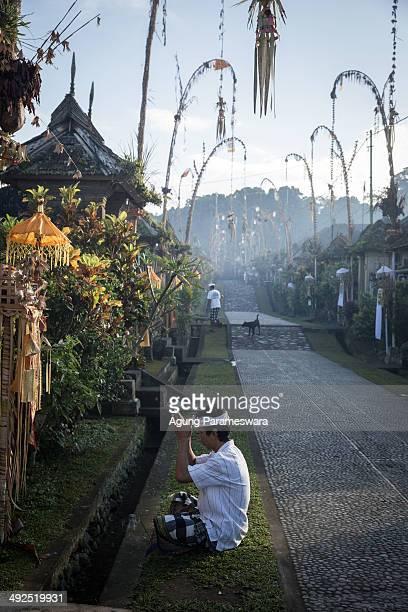 Balinese Hindus man prays infront of his home as he celebrate Galungan Day at Pengelipuran Village on May 21 2014 in Bangli Bali Indonesia Galungan...