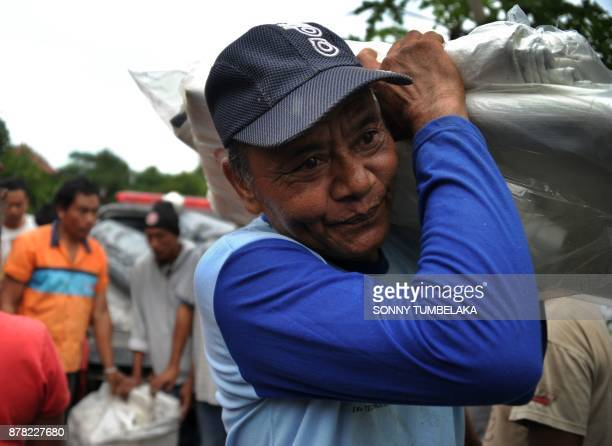 A Balinese man carries materials used for a makeshift evacuation centre in the Rendang subdistrict of Karangasem Regency as fears of a larger scale...
